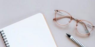 Notebook and pencil next to folded pair of glasses