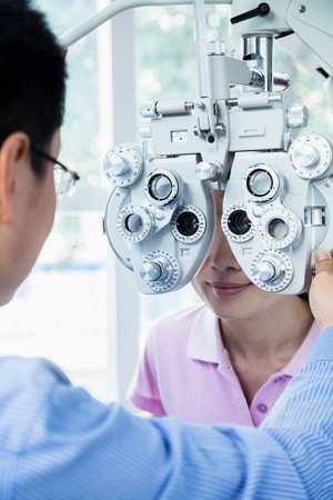 Wearing looking through eye exam equipment